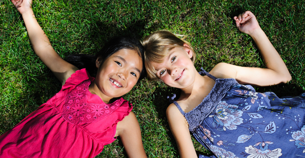 Two kids laying on the grass side by side